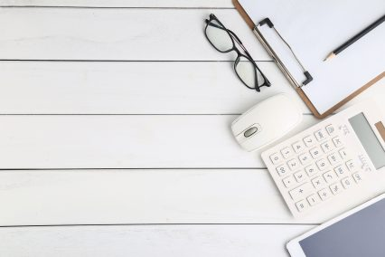 glasses, calculator and tablet on white neat desk